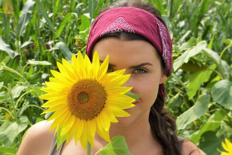 Beautiful girl hiding behind a sunflower